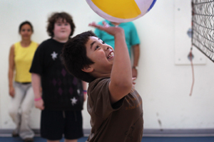 Boy hitting a beach ball in an indoor gym.