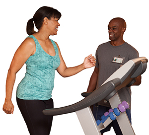 Man coaching woman walking on treadmill.