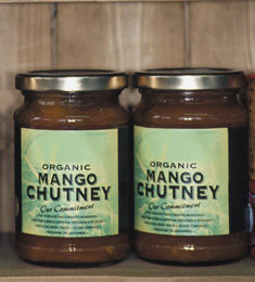 Two jars of mango chutney sitting on a shelf.