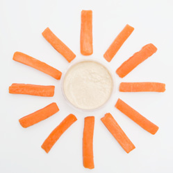 Small bowl of hummus surrounded by carrot sticks spread around it like rays of sunshine.
