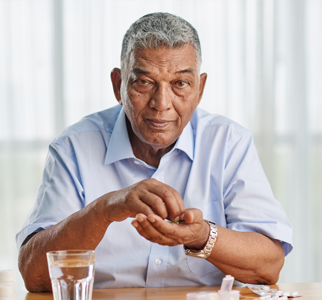 Older man sitting at kitchen table with medicines and glass of water